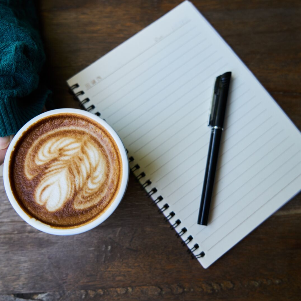 A cup of coffee with a notebook and pen.